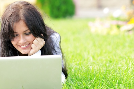 Young beautiful smiling woman using laptop on campushome yard. Sunny day. Stock Photo