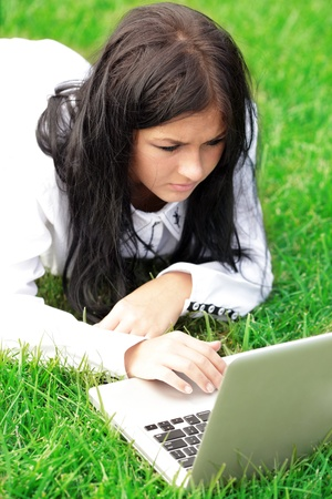 Young woman working on laptop. Lying on green lawn photo