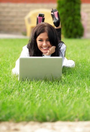 Young beautiful smiling woman using laptop on campushome yard. Sunny day. photo