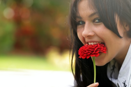 Mad woman eating a flower in the park Stock Photo - 9282578