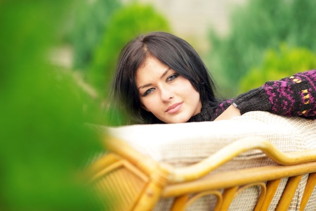 Young Beautiful Woman in Sweater Relaxing on the Sofa In Garden. Looking to the Camera.  photo
