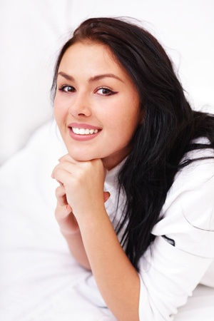 Closeup portrait of a happy young beautiful woman lying on the bed photo