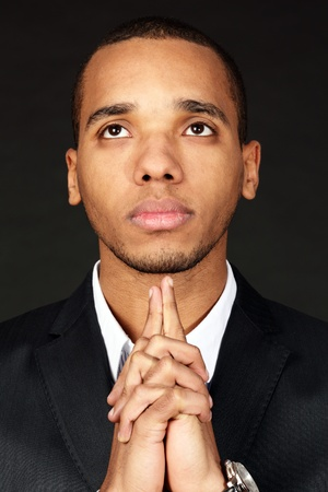 Closeup portrait of a young pensive african-american businessman over dark background Stock Photo - 9283092