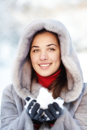 Cute young woman playing with snow in fur coat outdoors Stock Photo - 9282967