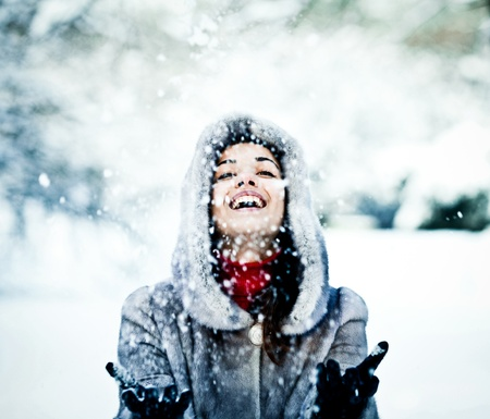 Cute young woman playing with snow in fur coat outdoors photo