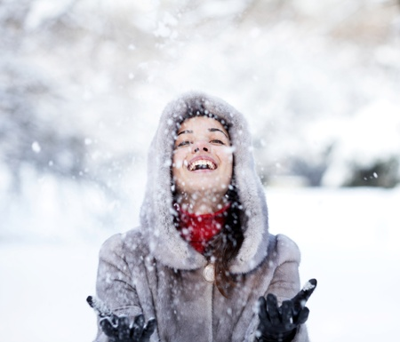Cute young woman playing with snow in fur coat outdoors Stock Photo - 9282457