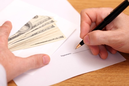 signing a contract: Businessman signing a contract and getting money for it
