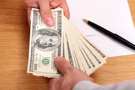 Uomini d'affari che passa soldi con contratto sullo sfondo
