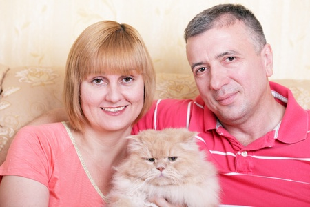 A happy family enjoying their free time at home with fluffy cat photo