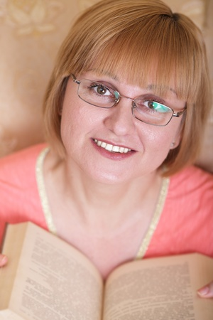 A happy woman in eyeglasses reading a book photo