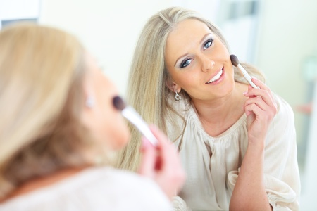 Young beautiful woman smiling to herself in mirror Stock Photo