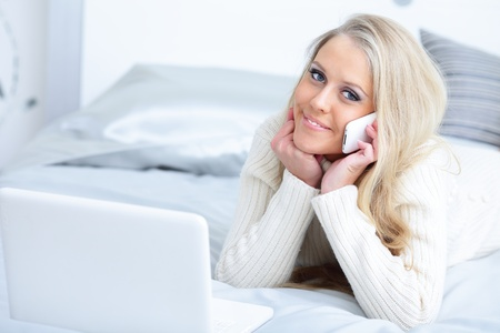 Young beautiful laughing woman lying on the bed with laptop and phone Stock Photo - 9283279