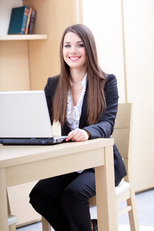 Attractive young business woman using laptop Stock Photo - 9365339