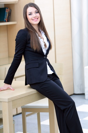 Young happy businesswoman in suit standing near the table in the office Stock Photo - 9365464