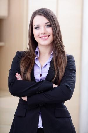 businesswoman suit: Joven empresaria feliz en el cargo con los brazos cruzados