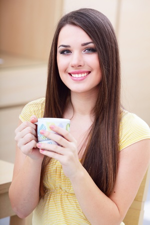 Young happy woman drinking a cup of tea