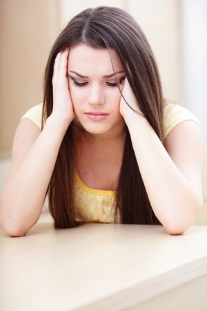 Woman with a headache sitting at home near the table photo