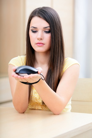 Young woman sitting at home with hands tied with computer mouse cable. photo