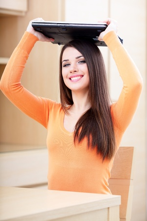 Young happy woman covering her head with a laptop Stock Photo - 9365508