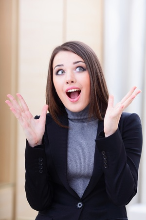 Very happy and surprised young beautiful businesswoman photo