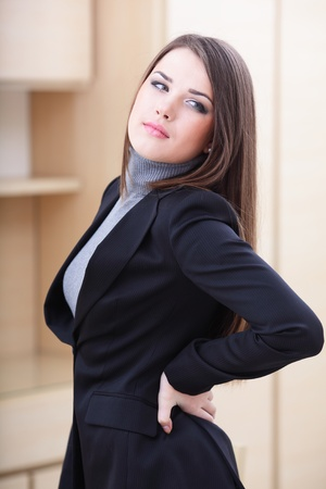 Young business woman in office holding her lower back in pain photo