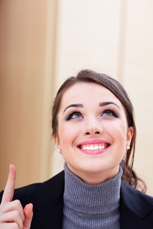 Portrait of young business woman pointing up at copyspace photo