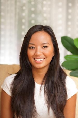 mujeres sentadas: Asia feliz joven sentado en la sala de estar sonriendo