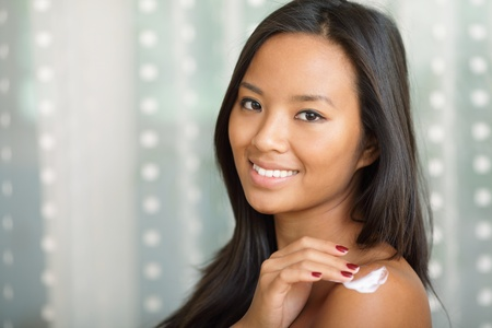 Portrait of a beautiful asian woman putting cream on her shoulder photo