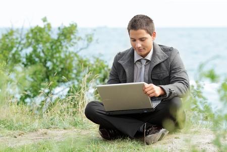 Man using a laptop outdoors photo