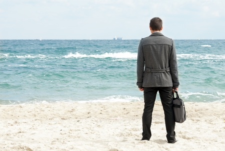 Image of young businessman on the beach photo