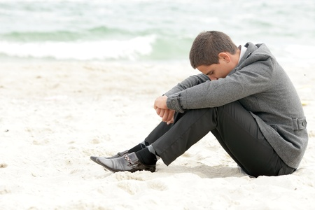 pensive man: A businessman sitting on the beach depressed Stock Photo