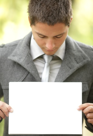 Young businessman holding a blank sign with copyspace photo