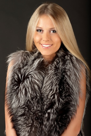 arctic fox: Happy beautiful woman in fur clothings, isolated over dark background