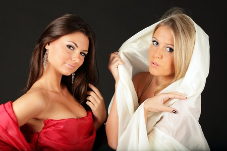 Two women expressing opposite characters on black background photo