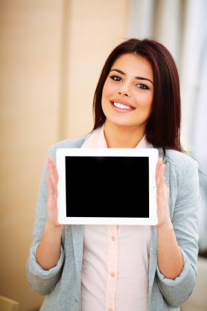 Young beautiful businesswoman showing ipad where you can put your image or text photo