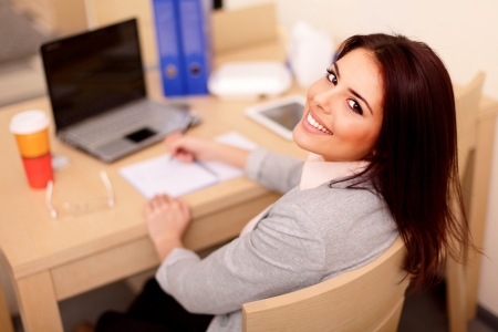 working: Young businesswoman sitting at desk and working. Smiling and looking back at camera