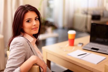 businesswoman suit: Joven empresaria sentado en el escritorio y trabajar. Sonriente y mirando a c?ra Foto de archivo