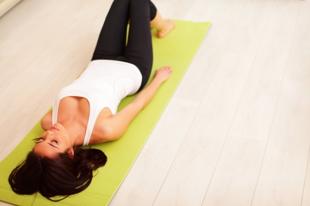 Young woman in sport cloths lying on the yoga mat photo