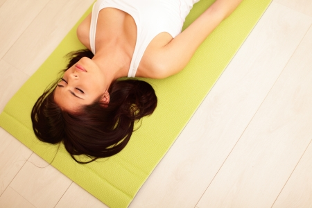 mat: Young woman in sport cloths lying on the yoga mat