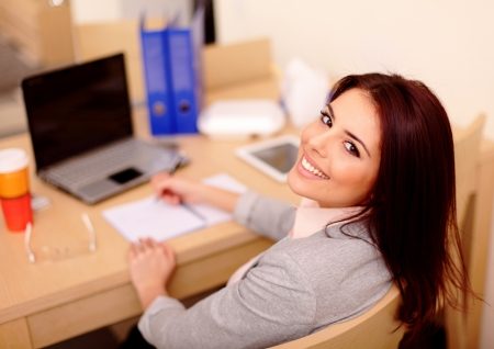 Young businesswoman sitting at desk and working  Smiling and looking back at camera photo