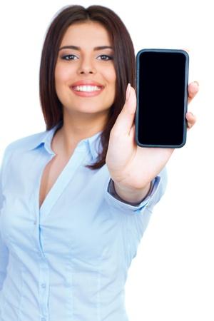 celulas humanas: Mujer joven que muestra la pantalla del tel�fono celular m�vil con pantalla en negro y sonriente sobre un fondo blanco. Foco en la mano.