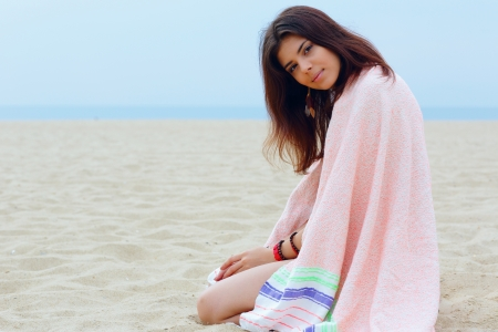 Young beautiful woman wrapped herself with blanket on the beach photo