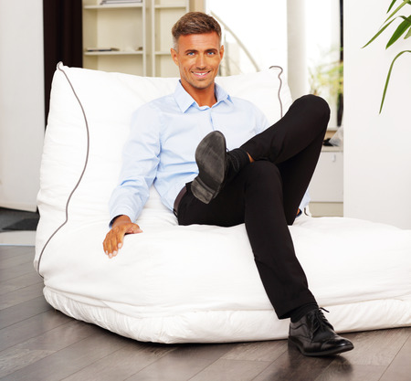 Handsome confident man sitting in armchair at home