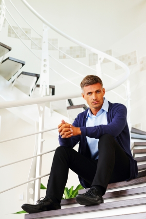 Mature pensive man sitting on stairs at home photo