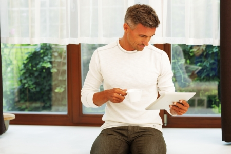 Happy young man at home drinking coffee and reading news on his electronic tablet photo