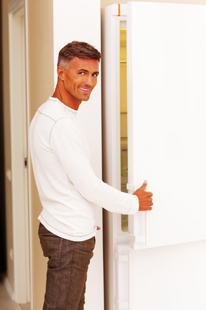 Handsome happy man opening the refrigerator Stock Photo - 22532700