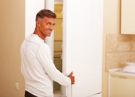 Handsome happy man opening the refrigerator Stock Photo - 22532701