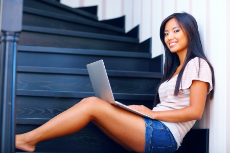 Young beautiful asian woman using laptop on stairs at home photo