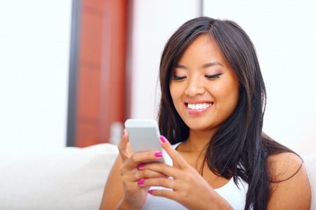 text room: Beautiful young asian woman text messaging with her smart phone at home
