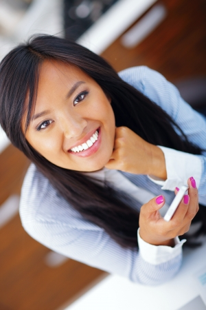 Young happy asian woman using her smartphone photo